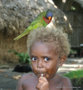 another child with lollipop and pet parakeet