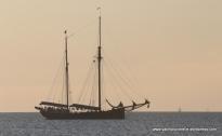 Tall ship passing at sunset