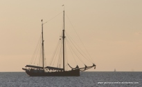 Tall ship passing at sunset